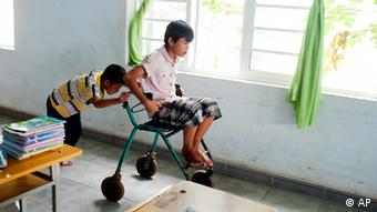 A Vietnamese boy pushes another boy in a wheelchair