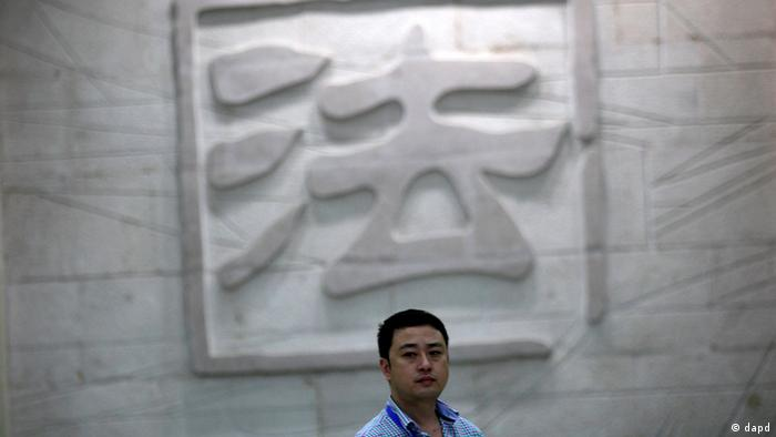 A man walks in front of the engraved wall depicting a Chinese character that means law inside the Hefei City Intermediate People's Court where a murder trial of Gu Kailai, wife of disgraced Chinese politician Bo Xilai, takes place Thursday Aug. 9, 2012 in Hefei, Anhui Province, China. The court heard in the one-day trial that Gu got British businessman Neil Heywood drunk and fed poison to him. (Foto:Eugene Hoshiko/AP/dapd)