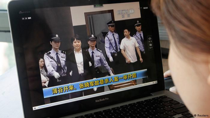 A woman watches a CCTV video showing Gu Kailai being escorted into the court room for trial at Hefei Intermediate People's Court