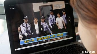 A woman watches a CCTV video showing Gu Kailai being escorted into the court room for trial at Hefei Intermediate People's Court, on a laptop in Beijing August 9, 2012. Gu Kailai, the wife of ousted Chinese Communist Party Politburo member Bo Xilai, did not raise objections in court on Thursday to charges against her of murdering a British businessman, a court official said. REUTERS/Jason Lee (CHINA - Tags: POLITICS CRIME LAW TPX IMAGES OF THE DAY)