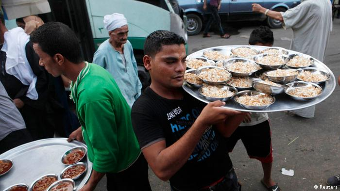 Volunteers carry food for an Iftar meal