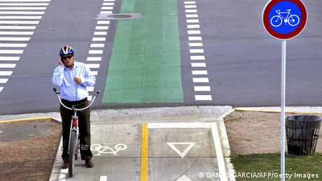 A man stops to use his mobile phone as he rides his bicycle along a bike path in Buenos Aires, on April 28, 2011. A program of the government of the city of Buenos Aires to encourage cycling as a means of transportation in the metropolitan area has had an uneven result. Some new bike paths are in good condition and marked, but older ones are generally in poor condition, hampering the traffic of cars, buses and trucks, and furthermore, two-way bike lanes built on one-way streets have caused incidents with pedestrians who tend to look only towards the side of vehicular traffic. Also, pedestrians in general are not accustomed to bike paths and do not respect them, using them as an extension of the sidewalk. AFP PHOTO/DANIEL GARCIA (Photo credit should read DANIEL GARCIA/AFP/Getty Images)