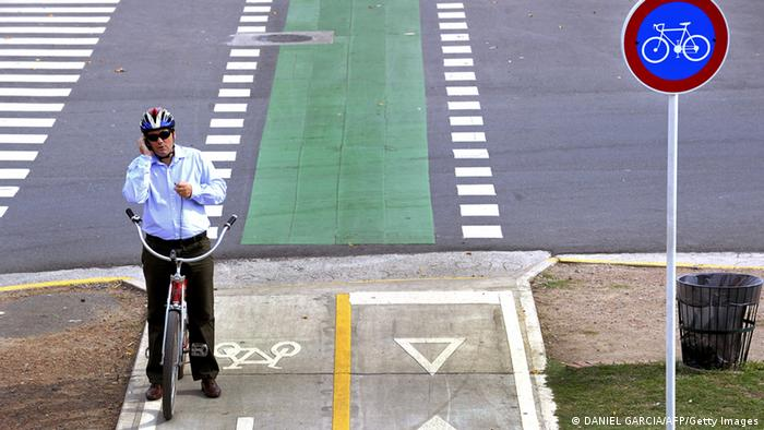 A man stops to use his mobile phone as he rides his bicycle along a bike path in Buenos Aires (DANIEL GARCIA/AFP/Getty Images)