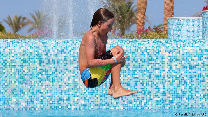 Ein Junge springt mit angezogenen Knien ins Wasser