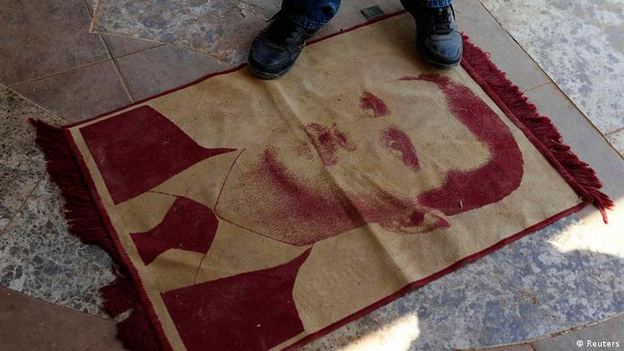 A man steps on a carpet with an image of Syrian President Bashar Assad