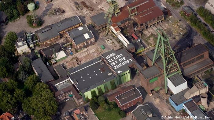 Крыша заброшенной угольной шахты в Динслакене с надписью Was bleibt ist die Zukunft