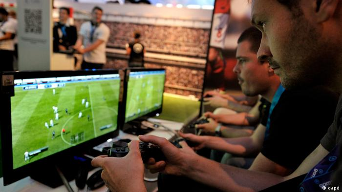 Two men play Fifa at Gamescom in Cologne (Copyright: Sascha Schuermann/dapd)