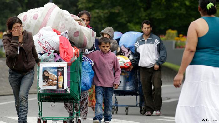 Roma families push shopping carts with their belongings as they are evicted from an illegal camp in Villeneuve d'Ascq August 9, 2012. French police evacuated some 150 people who resided in an illegal camp of travelling people and Roma in northern France. REUTERS/Pascal Rossignol (FRANCE - Tags: POLITICS SOCIETY IMMIGRATION)