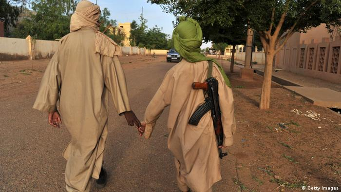Two young fighters of the Islamist group Movement for Oneness and Jihad in West Africa (MUJAO) walk in the streets of Gao on July 17, 2012. A group of armed youths has arrived in Gao from Burkina Faso, joining hundreds of other young African recruits who have come to sign up with radical Islamists controlling the northern Mali town. AFP PHOTO / ISSOUF SANOGO (Photo credit should read ISSOUF SANOGO/AFP/GettyImages)