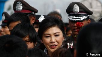 Thailand's Prime Minister Yingluck Shinawatra greets people as she visits new flood gates (Photo: REUTERS/Sukree Sukplang)