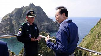 South Korean President Lee Myung-bak, right, talks with police officer Yoon Jang-soo on an Aug. 10 visit to the islands