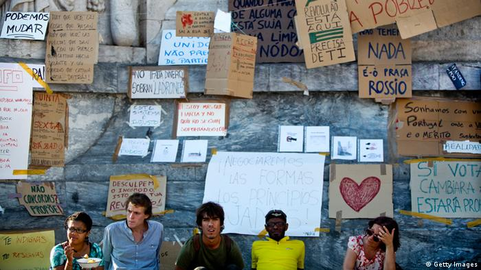 Portuguese youths sit in front of myriad banners AFP PHOTO / PATRICIA DE MELO MOREIRA (Photo credit should read PATRICIA DE MELO MOREIRA/AFP/Getty Images)