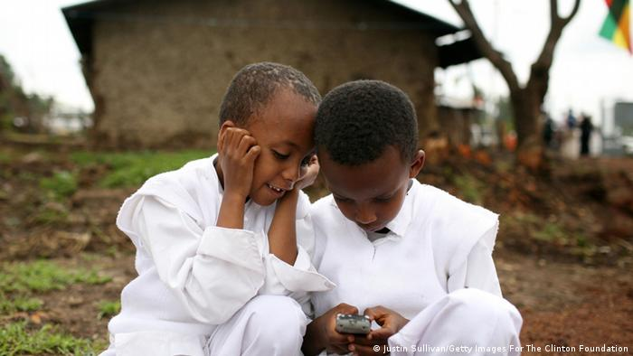 Two children in Ethiopia play with a mobile phone.