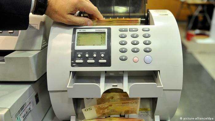 A Lebanese bank employee uses a machine to count European currency at a Bank in Beirut