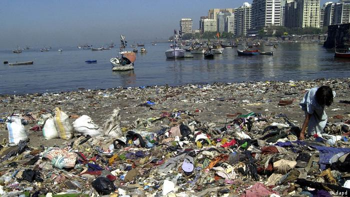 Fishing boats stand anchored as a young girl from a nearby slum rummages through a garbage littered beach in Bombay, India, Sunday, March 13, 2005 (ddp images/AP Photo/Rajesh Nirgude)