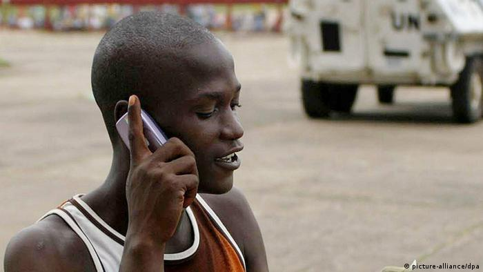 A man using a cell phone on the street in Liberia. (Photo: Ahmed Jallanzo/EPA dpa)
