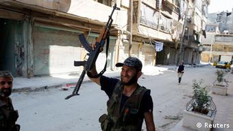A Free Syrian Army fighter holds up his rifle in the Salaheddine neighbourhood of central Aleppo August 10, 2012.