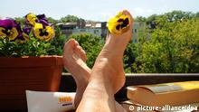 Symbolfoto Urlaub auf Balkonien: Eine Frau sitzt am Montag (14.05.2012) in Düsseldorf mit Büchern und Sonnencreme auf einem Balkon und streckt ihre Beine der Sonne entgegen. Urlaub auf Balkonien heißt - die Leute verreisen nicht sonder verbringen den Urlaub auf ihrer Terrasse oder auf dem Balkon. Foto: Horst Ossinger dpa