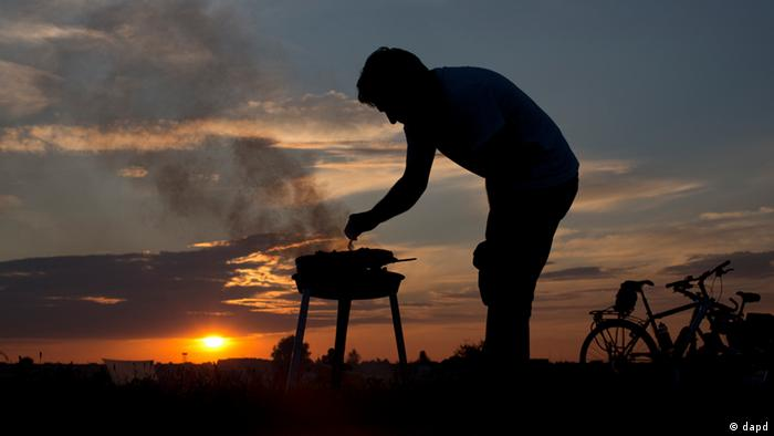 A man checks his barbecue as the sun sets at the former Tempelhof city airport, which became a public recreation area after its shutdown, in Berlin, Germany, Saturday, Aug. 4, 2012. (Foto:Gero Breloer/AP/dapd)