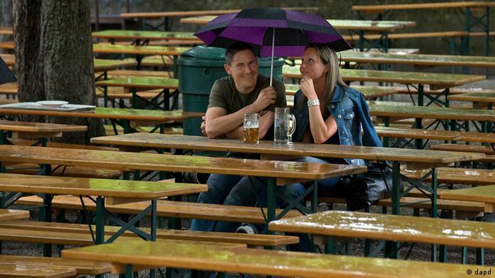 Zwei Menschen sitzen bei Regenwetter unter Regenschirmen auf Holzbänken