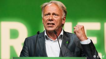 Jürgen Trittin raises his left hand mid-speech in front of a green background. (Photo: Clemens Bilan/dapd)
