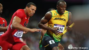 Usain Bolt of Jamaica receives the relay baton from Yohan Blake of Jamaica next to Ryan Bailey of the United States