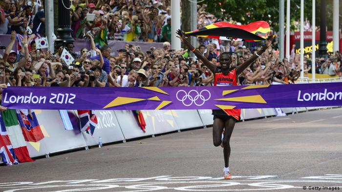 Uganda's Stephen Kiprotich waves his national flag as he crosses the finish line to win the athletics event men's marathon during the London 2012 Olympic Games on August 12, 2012 in London. DANIEL GARCIA/AFP/GettyImages