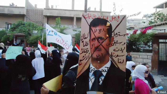 Anti Bashar Assad banner held up by protesters in Damascus suburb