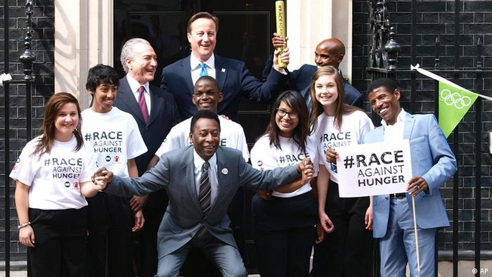 Brazilian soccer great Brazilian Pele, forground, with Brazilian Vice-President Michel Temer, rear left, Britain's Prime Minister David Cameron centre rear, Britain's double Olympic Champion Mohamed Farah, rear right), Ethiopian runner Haile Gebrselassie, right, and youngsters pose outside 10 Downing Street in London Sunday Aug. 12, 2012. Farah the Somalia-born athlete has been invited to join international politicians and other sporting greats at the event which is designed to shine the spotlight of the Games on the issue of child malnutrition. (AP Photo/ Max Nash/PA) UNITED KINGDOM OUT NO SALES NO ARCHIVE