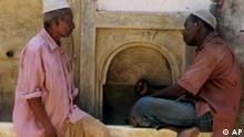 Zwei Moslems sitzen auf der Insel Lamu an einem Brunnen und unterhalten sich Kenia