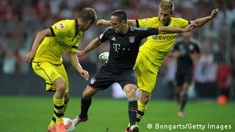MUNICH, GERMANY - AUGUST 12: Lukasz Piszczek of Dortmund and teammate Jakub Blaszczykowski challenge Franck Ribery of Bayern during the Bundesliga Supercup 2012 match between Bayern Muenchen and Borussia Dortmund at Allianz Arena on August 12, 2012 in Munich, Germany. (Photo by Dennis Grombkowski/Bongarts/Getty Images)