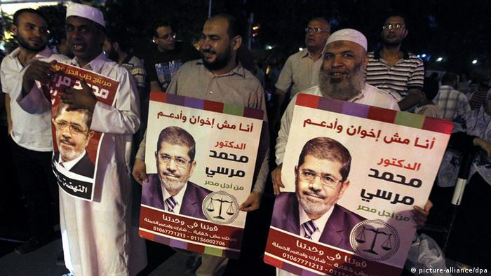 epa03360878 Hundreds of supporters celebrate with posters showing Egypt's President Mohamed Morsi in front of the Presidential palace, in Cairo, Egypt, 12 August 2012. According to media reports on 12 August 2012, Egyptian President Morsi ordered the head of the army and defence minister, Field Marshal Tantawi and Chief of Staff Anan, into retirement and cancelled a constitution issued by the military restricting presidential powers. EPA/KHALED ELFIQI