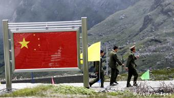 NATHU LA PASS, INDIA: A group of Chinese army officers walk past a display board on the Chinese part of the Indo-Chinese border of Nathu La, some 52 kilometres (33 miles) east of Gangtok, 05 July 2006. Formal trading is due to begin at the 15,000-foot (4,545 metre) Nathu La Pass on the border between India's Sikkim state and China's Tibet region, 06 July 2006. Indian businessmen and local people expect a change in the region's economy patterns following the formal resumption of trade between India and China when the Nathu La Pass, along the historic Silk Route, re-opens on the border. AFP PHOTO/ Deshakalyan CHOWDHURY (Photo credit should read DESHAKALYAN CHOWDHURY/AFP/Getty Images)