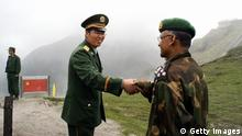 NATHU LA PASS, INDIA: A Chinese army officer (L) exchanges greetings with his Indian counterpart following a meeting among the officers, as they stand on the border of Nathu La, some 52 kilometres (33 miles) east of Gangtok, 05 July 2006. Formal trading is due to begin at the 15,000-foot (4,545 metre) Nathu La Pass on the border between India's Sikkim state and China's Tibet region. Indian businessmen and local people expect a change in the region's economy patterns following the formal resumption of trade between India and China when the Nathu La Pass, along the historic Silk Route, re-opens. AFP PHOTO/ STR (Photo credit should read STRDEL/AFP/Getty Images)