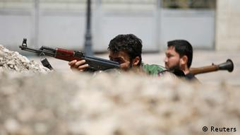 Free Syrian Army fighters sit behind a barricade on a street in Aleppo