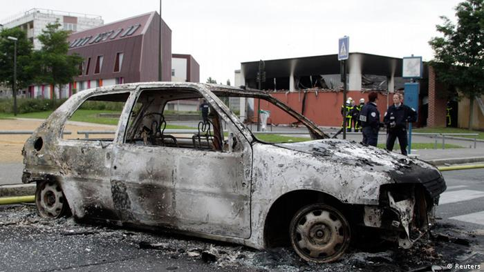 The shell of a burned out car in Amiens, France, after rioting there Monday, August 14.