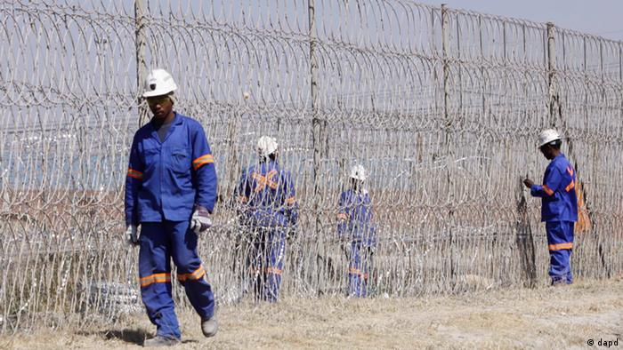 Workers install razor wire at the Lonmin platinum mine(Photo:Denis Farrell/AP/dapd)