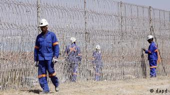 Workers install razor wire at a plant at the Lonmin Platinum mine near Rustenburg, South Africa, Tuesday Aug. 14, 2012.