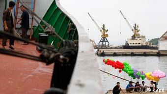 North Koreans rest at a send off ceremony for a North Korean leisure boat from the port in Rason city