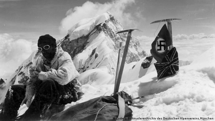 A mountaineer at a summit with a Nazi flag in the background Photo: Ludwig Schmaderer. Archive Deutschen Alpenvereins, München.
