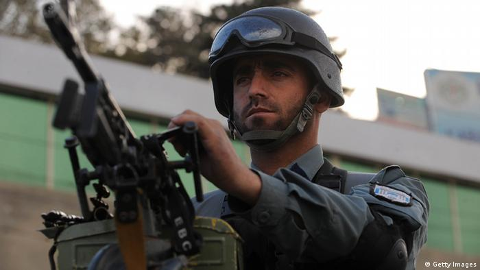 An Afghan policeman stands guard
