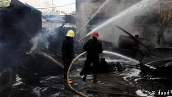 In this photo released by the Syrian official news agency SANA, firefighters extinguish fire at the scene after a bomb attached to a fuel truck exploded outside a Damascus hotel where U.N. observers are staying according to the Syria's state TV in Damascus, Syria, on Wednesday Aug. 15, 2012.