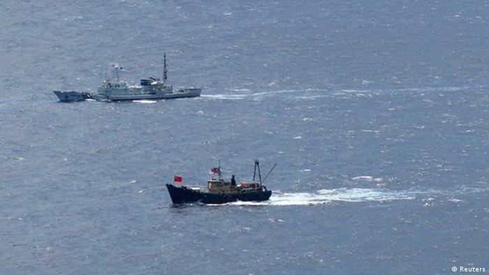 A Japan Coast Guard patrol ship sails around a fishing boat (R) carrying activists from the Hong Kong-based Action Committee for Defending the Diaoyu Islands near the disputed islands in the East China Sea, known as Senkaku in Japan or Diaoyu in China, in this handout photo taken by the Japan Coast Guard August 15, 2012. Bitter memories and current rivalries are straining Japan's ties with China and South Korea nearly seven decades after Tokyo's defeat in World War Two, raising the risk of ruptures as all three nations head for leadership changes. REUTERS/11th Regional Coast Guard Headquarters-Japan Coast Guard/Handout (JAPAN - Tags: POLITICS MARITIME) MILITARY FOR EDITORIAL USE ONLY. NOT FOR SALE FOR MARKETING OR ADVERTISING CAMPAIGNS