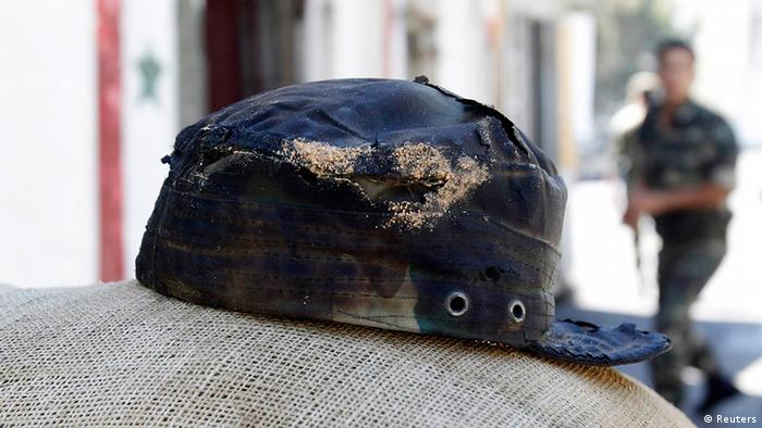 A burnt hat of a Syrian soldier is seen after a bomb exploded at a military site near a hotel used by United Nations monitors in Damascus August 15, 2012. A bomb exploded in Damascus on Wednesday near a hotel used by United Nations monitors and wounded three people, Syrian state television said on Wednesday. The bomb, which was placed in a car park behind the hotel, blew up a fuel truck which sent clouds of black smoke into the sky above the capital. REUTERS/Khaled al-Hariri (SYRIA - Tags: POLITICS CIVIL UNREST CONFLICT MILITARY)