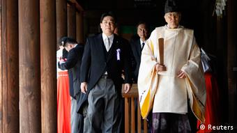 Tourism Minister Yuichiro Hata (center) and other lawmakers are led by a Shinto priest at the shrine