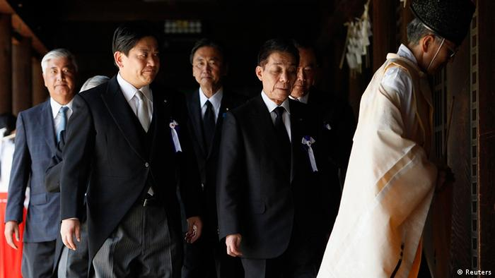 Japan's Land, Infrastructure, Transport and Tourism Minister Yuichiro Hata (2nd L) and other lawmakers are led by a Shinto priest after offering prayers to war dead at Yasukuni Shrine in Tokyo August 15, 2012, on the 67th anniversary of Japan's surrender in World War II. Japanese cabinet members paid homage at a controversial shrine for war dead on Wednesday -- the 67th anniversary of Tokyo's defeat in World War Two -- a move likely to further strain relations with China and South Korea. REUTERS/Issei Kato (JAPAN - Tags: ANNIVERSARY CONFLICT POLITICS)