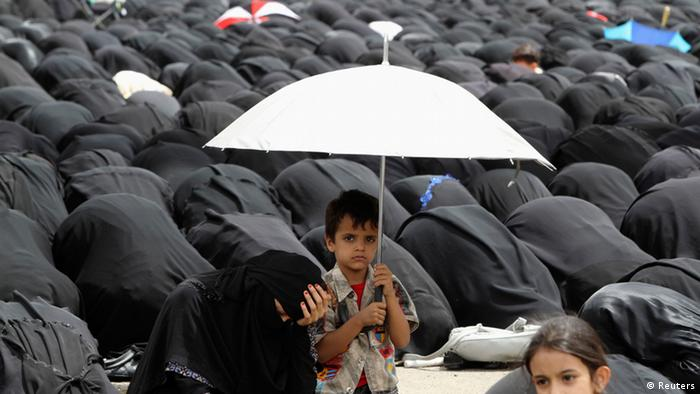Source News Feed: EMEA Picture Service ,Germany Picture Service A boy holds an umbrella as he sits next to his mother during prayers, as protesters demonstrate outside the home of Yemeni President Abd-Rabbu Mansour Hadi, demanding the dismissal of the rest of former president Ali Abdullah Saleh's family members from senior army and police positions, in Sanaa August 10, 2012. The protesters are in favour of the president's latest orders to restructure some military units on Monday. REUTERS/Mohamed al-Sayaghi (YEMEN - Tags: POLITICS CIVIL UNREST RELIGION)