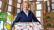 Sonne Leddin, Gründerin von Medikamente für Menschen in Not trägt eine große Kiste in einem Lagerraum; Copyright: privat