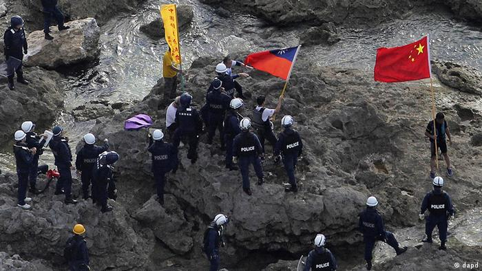 Activists holding Chinese and Taiwanese flags are arrested by Japanese police officers after landing on Uotsuri Island, one of the islands of Senkaku in Japanese and Diaoyu in Chinese, in East China Sea Wednesday, Aug. 15, 2012. Regional tensions flared on the emotional anniversary of Japan?s World War II surrender as activists from China and South Korea used Wednesday?s occasion to press rival territorial claims, prompting 14 arrests by Japanese authorities. The 14 people had traveled by boat from Hong Kong to the disputed islands controlled by Japan but also claimed by China and Taiwan. (Foto:Yomiuri Shimbun, Masataka Morita/AP/dapd) JAPAN OUT, MANDATORY CREDIT
