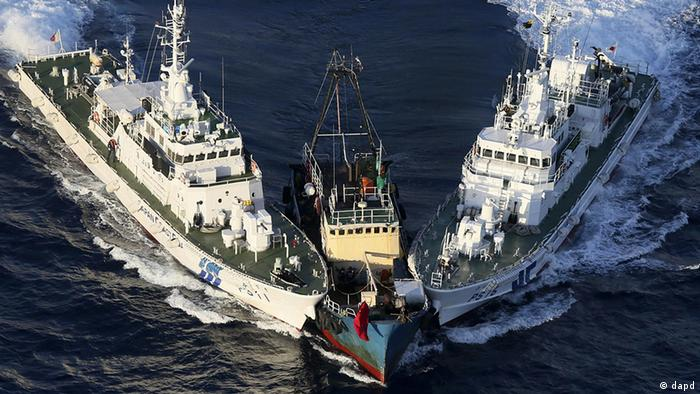 A boat, center, is surrounded by Japan Cost Guard's patrol boats